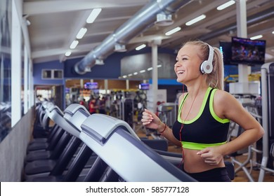 Sport blonde girl smiling happy on the treadmill in the gym