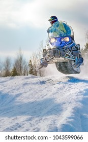 Sport blue snowmobile jump. Cloud of snow dust from under snowmobile tracks. Extreme sport background for any purposes. Front view, vertical shot. Copy space.