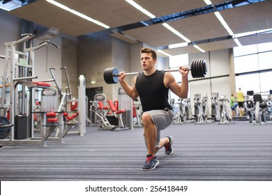 sport, bodybuilding, lifestyle and people concept - young man with barbell flexing muscles and making shoulder press lunge in gym
