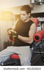 sport, bodybuilding, lifestyle, technology and people concept - young man with smartphone in gym