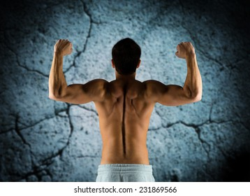 sport, bodybuilding, strength and people concept - young man showing biceps and muscles over concrete wall background