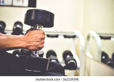 sport, bodybuilding, training and people concept , young man with dumbbell flexing muscles in Fitness Room.