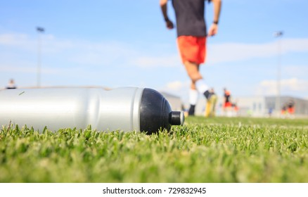 Sport bottle of fresh water energy drink on football field grass.