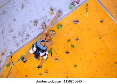 sport. bouldering - girl climbing up the wall