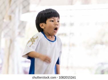 Sport boy in soccer jersey with asthma is coughing and breathing hard on the field. For Children Sport Healthy Medical concept