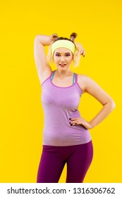 Sport camisole. Appealing blonde-haired young woman wearing bright leggings and sport camisole