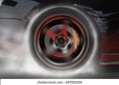 Sport car burning rear tire to heat up rubber for good traction before start to race.