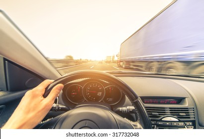 sport car overtaking a truck on the highway. concept about transportation, cars and safety on the street