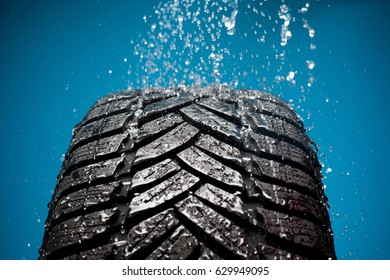 sport car tire with water drops against black