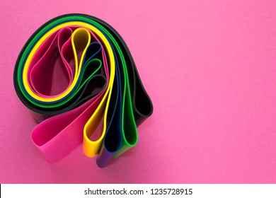 Sport concept - set of colorful fitness elastic expanders for woman on pink background. Healthy lifestyle and weight loss. Copy space for text.