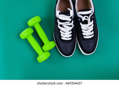 Sport concept, sneakers and dumbbells over green background, top view