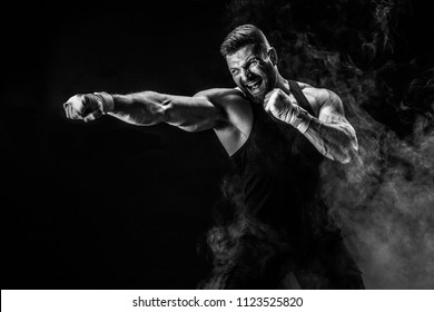 Sport concept. Sportsman muay thai boxer fighting on black background with smoke.