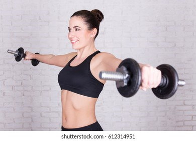 sport concept - young beautiful woman doing exercises with dumbbells over white brick wall