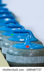 Sport Concepts. Closeup of Curling Blue Handle Stones on Ice.With Copyspace. Vertical Image Composition