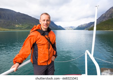 Sport couple hiking on Besseggen. Hikers enjoy beautiful lake and good weather in Norway