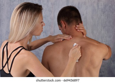 Sport couple, man suffering from back pain,woman applying pain relief cream on man's back