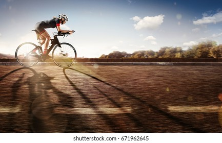 Sport. The cyclist rides on his bike at sunset. Dramatic background.