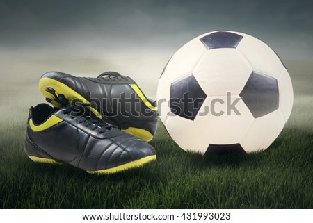 b7f95f46a Sport equipment concept of a ball and soccer shoes in football field under  the sky