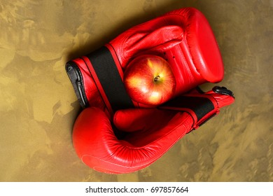 Sport equipment and fruit on dark beige marble background. Pair of leather boxing sportswear with juicy red apple. Knock out and healthy nutrition concept. Boxing gloves in red color