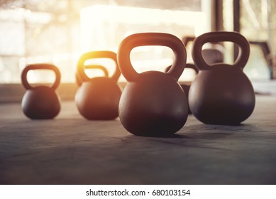 Sport equipment in gym. Kettlebell on floor background with sunlight effect. Fitness training