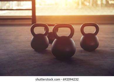 Sport equipment in gym. Kettlebell on floor background with sunlight effect. Fitness training.