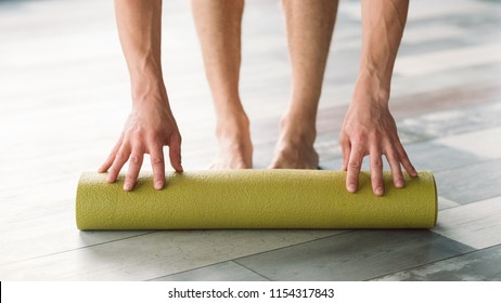 sport equipment. handy and useful yoga mat for the best training performance. unrecognizable man rolling out a mat to start exercising. health and fitness concept.