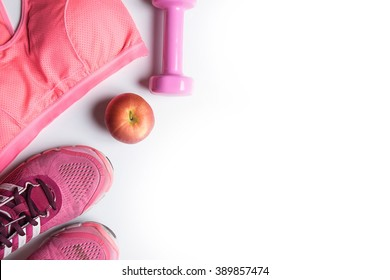 Sport equipment. Sneakers, apple, pink top on white background top view.