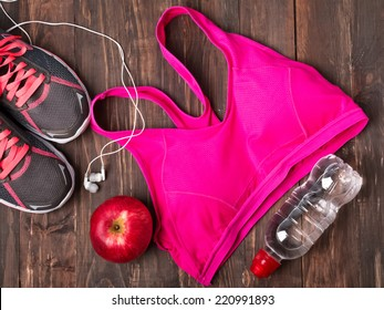 Sport equipment. Sneakers, water, pink top and earphones  isolated on white background