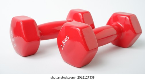 Sport equipment. Two red dumbbells weighing 2 kg on a white background.