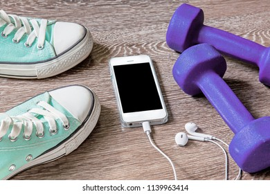 Sport equipments. Smartphone and sport shoes on wood floor.