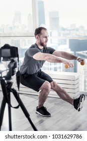 Sport for everyone. Bearded attractive male blogger holding dumbbells while rising leg and performing exercise