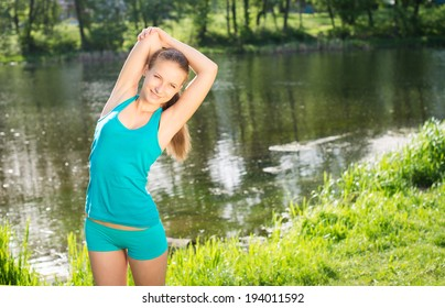 Sport, exercise and healthcare. Girl doing fitness near river.
