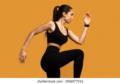 Sport Exercises And Healthy Lifestyle. Side View Portrait Of Determined Slim Young Lady Running And Sprinting, Wearing Fitness Bracelet, Lifting Leg Up, Exercising Isolated On Orange Studio Background