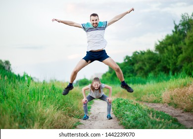 Sport family portrait of handsome father and his cute little daughter play leap frog outdoor at sunset