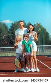 Sport family smiling. Good-looking sport family smiling while standing on tennis court with tennis rackets
