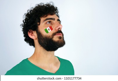 Sport fan head high and feeling proud when listening to the anthem of his country. Man with the flag of Mexico makeup on his face and green t-shirt.