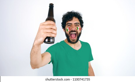Sport fan holding a beer screaming for the triumph of his team. Man with the flag of Mexico makeup on his face and green t-shirt. CONMEBOL Copa America
