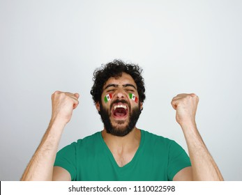 Sport fan screaming celebrating the triumph of his team. Man with the flag Mexico makeup on his face and green t-shirt.