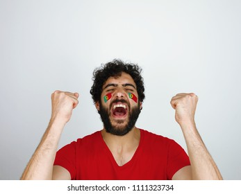 Sport fan screaming celebrating the triumph of his team. Man with the flag of Portugal makeup on his face and red t-shirt.