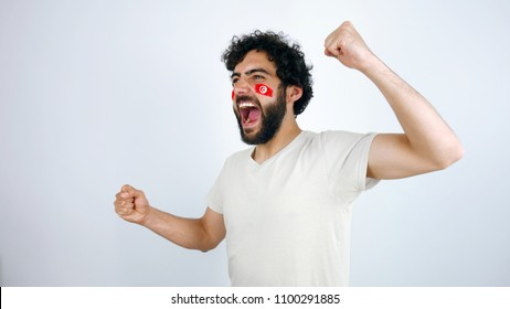 Sport fan screaming for the triumph of his team. Man with the flag of Tunisa makeup on his face and white t-shirt.