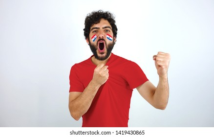 Sport fan screaming for the triumph of his team. Man with the flag of Paraguay makeup on his face and red t-shirt.