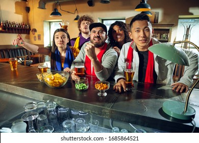 Sport fans cheering at bar, pub and drinking beer while championship, competition is going. Multiethnic group of friends excited watching translation. Human emotions, expression, supporting concept.