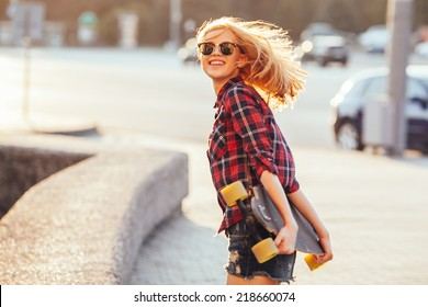 Sport fashion girl posing in summer with skateboard