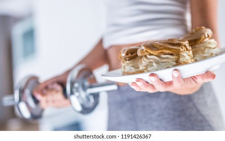 The sport figure of a attractive woman holding plate with high-calorie cakes and dumbbell.