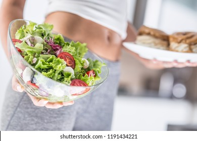 The sport figure of a attractive woman holding plate with high-calorie cakes and fresh vegetable salad.