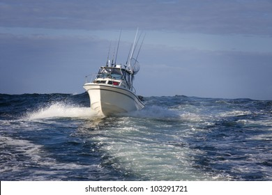 sport fishing boat cresting a wave on open ocean in the Pacific West Coast.