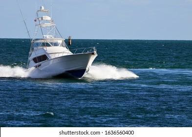 Sport fishing boat with flying bridge under full throttle of the Florida Intra-Coastal Waterway