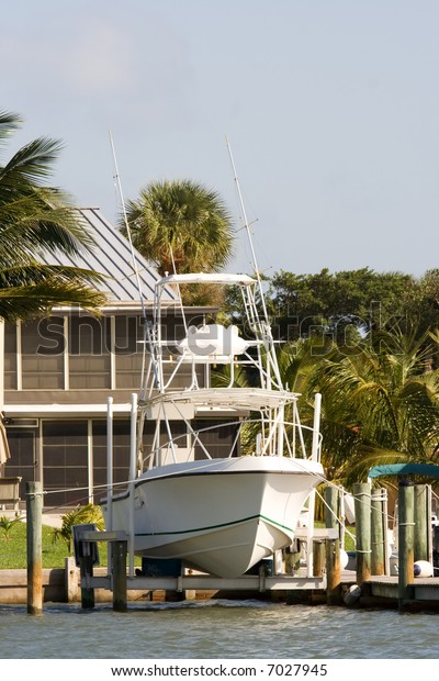 sport fishing boat on lifting dock outside house