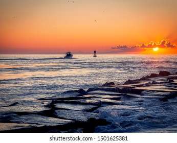 A sport fishing boat on a summer's dawn day heads out of Delaware's Indian River Inlet.