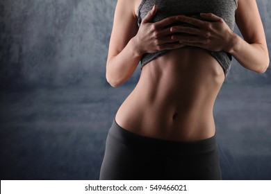 Sport, fit woman. Female with perfect abdomen muscles on grey background. Dieting, fitness, active lifestyle concept, copy space